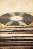 Vinylrekord på tornet av albumräkningar, texturerad bakgrund, retro blick Fotografering för Bildbyråer