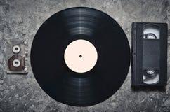 Vinylverslag, audio en videocassettes op een grijze concrete oppervlakte Retro media technologie van de jaren '80 Hoogste mening stock foto's
