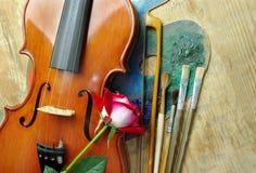Violín, cepillos, color de rosa y paleta en un fondo de madera Visión superior Imagen de archivo