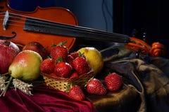 Violín con el cuello y fresas en una fruta de la cesta, mojada y jugosa Fotos de archivo libres de regalías