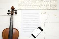 Violín con el teclado de la nota del papel de música y el teléfono elegante Fotografía de archivo libre de regalías