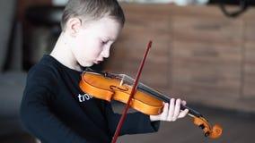 Violín del control de la manija Violín que lleva del niño pequeño Muchacho joven que toca el violín, jugador talentoso del violín almacen de video