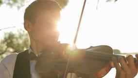 Violín del juego del hombre del violinista en la naturaleza en la puesta del sol almacen de metraje de vídeo