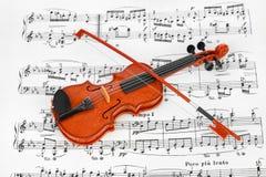 Violín del juguete y hoja de música Foto de archivo libre de regalías