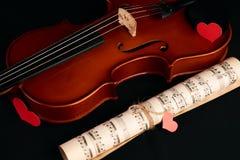 Violín, notas de la música y corazones rojos Fotos de archivo