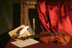 Violín, vela y pluma Imágenes de archivo libres de regalías