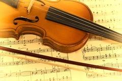 Violín viejo y notas musicales imagen de archivo