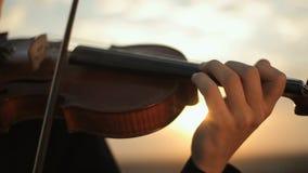 Violín Violinista que juega en la puesta del sol Secuencias y arco almacen de metraje de vídeo