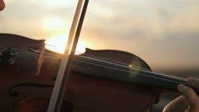 Violín Violinista que juega en la puesta del sol Violín y arco de las secuencias almacen de video