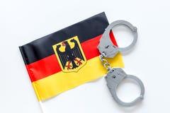 Violação da lei, lei-quebrando o conceito Algemas do metal na bandeira alemão na opinião superior do fundo branco foto de stock