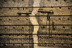 Violation of the secret code file - concept image with binary code agaist an old rusty metal door on wooden background.  stock image