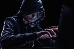 Violazione del concetto di diritti di proprietà intellettuale Pirata informatico in un cappuccio fotografia stock libera da diritti