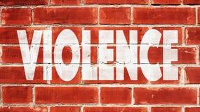 Violence écrite sur un mur de briques Photos stock