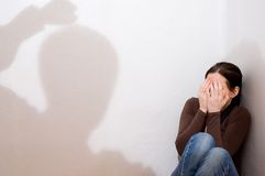 Violence. Woman sits in a corner, fearing violence royalty free stock image