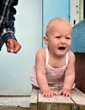 Violence against children. The little girl crying, because of the fact that her father hit her Stock Photo