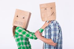 Violence against man. Aggressive woman with bag on head strangling her man. Negative relations in partnership. Violence against man. Aggressive women with bag Stock Images
