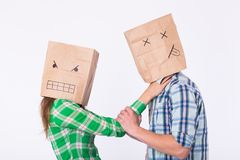 Violence against man. Aggressive woman with bag on head strangling her man. Negative relations in partnership. Violence against man. Aggressive women with bag Royalty Free Stock Images