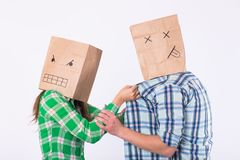 Violence against man. Aggressive woman with bag on head beating her man. Negative relations in partnership. stock images