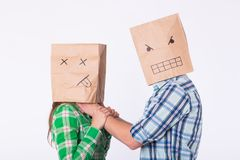 Violence against woman. Aggressive man with bag on head strangling his woman. Negative relations in partnership. Violence against woman. Aggressive men with bag Royalty Free Stock Photos