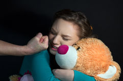 Violence in the family, hit the child on a dark background Stock Photos