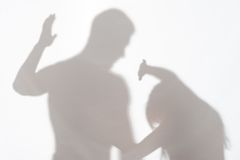 Violence of man against woman. Silhouette of men striking the women who cannot to protect herself Royalty Free Stock Photography