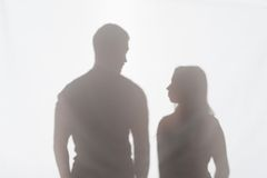 Violence of man against woman. Silhouette of men and women standing on white background and looking at each other Royalty Free Stock Image