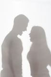 Violence of man against woman. Silhouette of men and women standing on white background and quarrelling Stock Photography