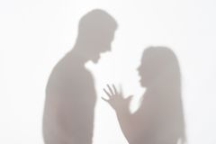 Violence of man against woman. Silhouette of men and women standing on white background and women wanted to explain something gesticulating with her hands Royalty Free Stock Photo