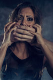 Violence. Young woman abuse victim with man's abuser hands on her mouth looking at camera Royalty Free Stock Photography