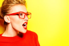 Violent behavior. Close-up portrait of a stunning female model in red dress and elegant spectacles posing over yellow background. Beauty, fashion, optics Stock Images