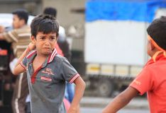 Violent Child. Angry boy fights other street children, in Mumbai, India, during clash, with brick in hand Stock Photo