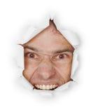 Violent evil man looks through a hole Royalty Free Stock Photo