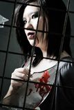 Violent female criminal looking through a grill. What goes on in a criminal mind royalty free stock images