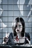 Violent female criminal looking through a grill Royalty Free Stock Image