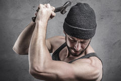 Violent man using a spanner as a weapon Stock Photo