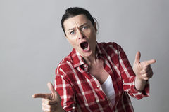Violent middle aged woman shouting with fighting hand gestures. With fingers shooting like guns in the foreground Stock Photos