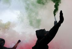 Violent protest with protesters. Dressed in black robes with green and red smoke Stock Photos