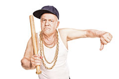 Violent senior with baseball bat giving a thumb down. Violent senior in hip-hop clothes holding a baseball bat and giving a thumb down isolated on white Royalty Free Stock Photography