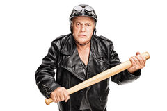 Violent senior biker holding a baseball bat. Angry and violent senior motorcyclist holding a baseball bat and looking at the camera isolated on white background Royalty Free Stock Image
