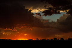 Violent Sunset. The sun dips below the horizon over the African wilderness after a violent thunderstorm Stock Photo