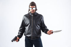 Violent young man holding a gun and a knife. Dangerous and violent criminal wearing cap and glasses is holding a gun and a knife in his hands - isolated on white Royalty Free Stock Image