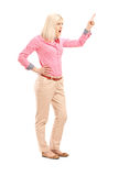 Violent young woman shouting and pointing with finger. Full length portrait of a violent young woman shouting and pointing with finger isolated on white Royalty Free Stock Photo