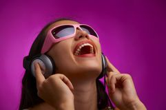 Violet beat. Glamour portrait of young brunette in pink sunglasses listening music Stock Photography
