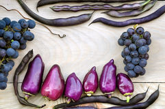 Violet bell peppers, purple beans, blue grapes on a light wooden background. Royalty Free Stock Photo