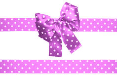 Violet bow and ribbon with white polka dots made from silk Royalty Free Stock Image