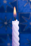 Violet candle on blue Stock Image