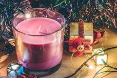Violet Candle, el ornamento y la Navidad adornan por noche de la Feliz Navidad y Feliz Año Nuevo Imágenes de archivo libres de regalías