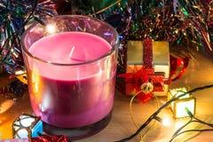 Violet Candle, el ornamento y la Navidad adornan por noche de la Feliz Navidad y Feliz Año Nuevo Imagen de archivo