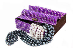 Violet casket with pearls. Violet casket with black and white pearls Stock Photo