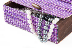 Violet casket with pearls. Violet casket with black and white pearls Stock Photography